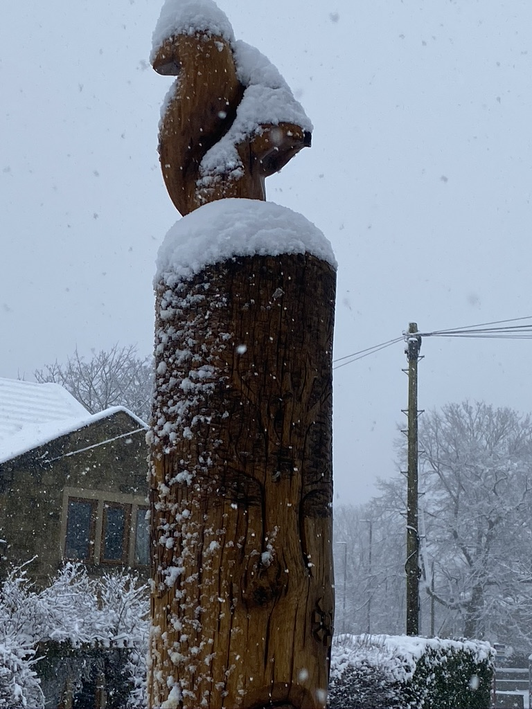 Wooden totem pole with wooden squirrel on the top covered in snow