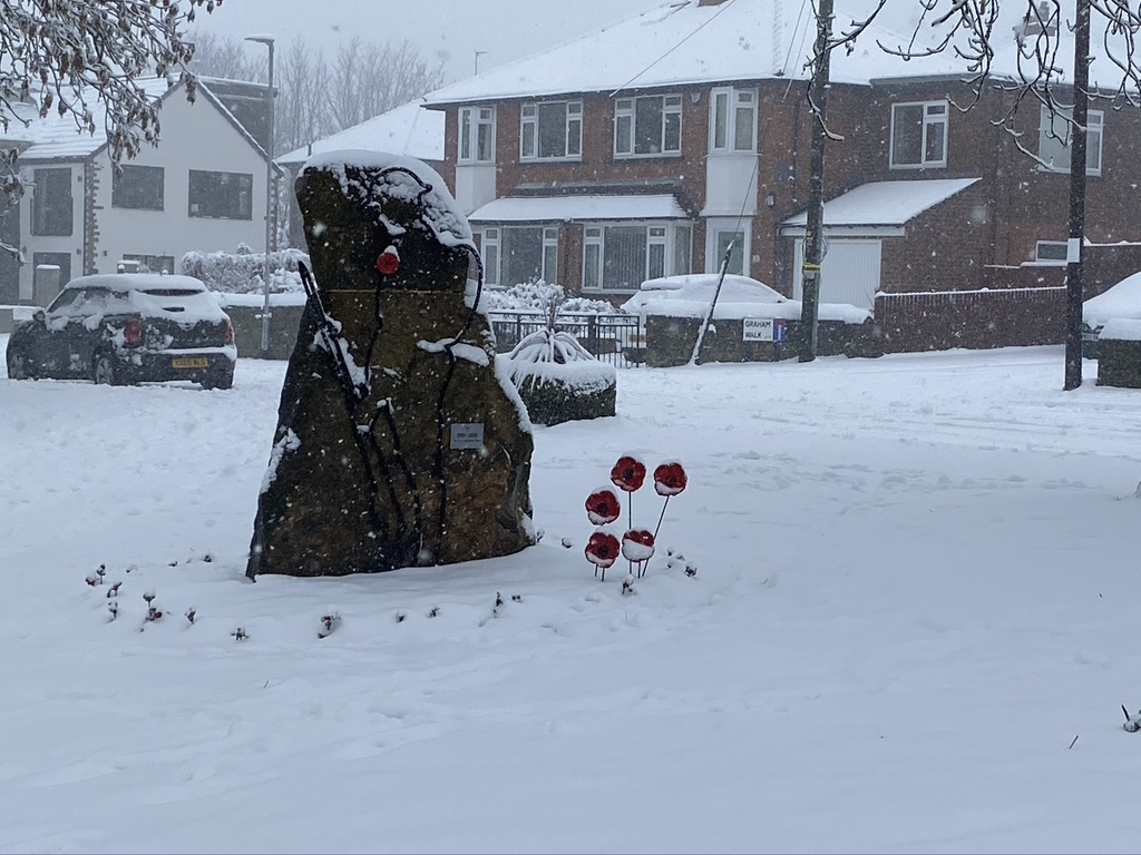 Stone war memorial with silhouette of a soldier surrounded with poppies and covered in snow